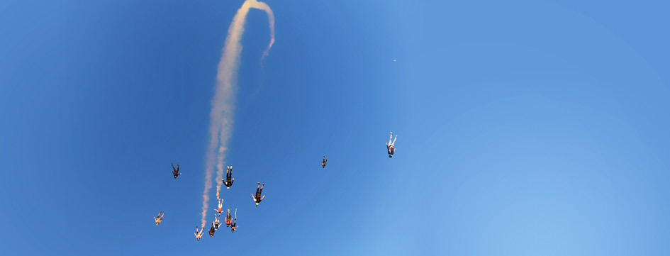 12 skydivers in a trace with smoke